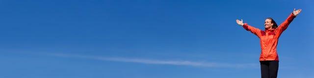 Vrouw het Vieren Wapens in Blauw Hemelpanorama dat worden opgeheven stock afbeelding