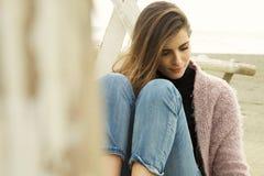 Vrouw het voelen alleen en gebroken hart denkende en schreeuwende zitting op strand Stock Foto