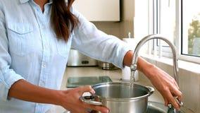 Vrouw het vullen pot met water Royalty-vrije Stock Afbeeldingen
