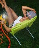 Vrouw het water geven met tuinslang Stock Foto's