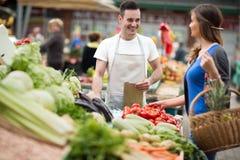 Vrouw het winkelen groente bij straatmarkt Stock Foto's