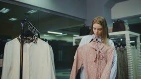 Vrouw het winkelen kijkt over kleding op hangers in de modieuze winkel van de klerenboutique stock video