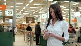 Vrouw het winkelen voedsel op supermarktachtergrond Sluit meningsmeisje opkopen producten gebruikend digitaal gadget in opslag Hi