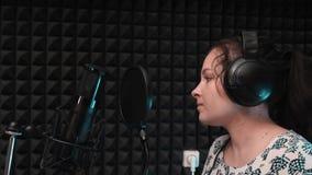 Vrouw het zingen in muziekstudio Zwarte microfoon en pop filter in muziekstudio stock videobeelden