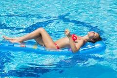 Vrouw het zwemmen en ontspant in de pool Stock Foto