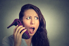 Vrouw hielde de het kijken opgewekte, verraste holding hoog schoen in haar hand als telefoon stock foto's