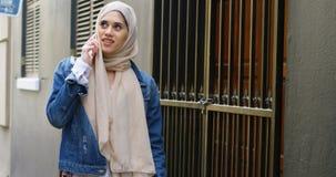 Vrouw in hijab die op mobiele telefoon spreken terwijl het lopen op de straat 4k stock video