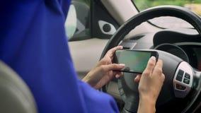 Vrouw in hijab het texting op telefoon achter het zelf-drijft stuurwiel van een autonome automatische piloot driverless auto stock videobeelden