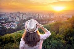 Vrouw in hoed bij de mening van de zonsondergangstad Stock Foto