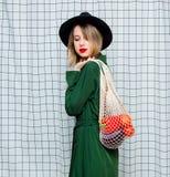 Vrouw in hoed en groene mantel in jaren '90stijl met netto zak stock foto