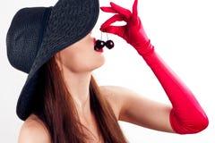 Vrouw in hoed en handschoenen die kersen eten royalty-vrije stock afbeelding