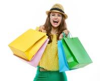 Vrouw in hoed en heldere kleren met zich het winkelen zakken het verheugen royalty-vrije stock afbeeldingen