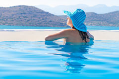 Vrouw in hoed het ontspannen bij zwembad Royalty-vrije Stock Afbeeldingen