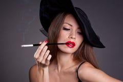 Vrouw in hoed met sigaret Stock Afbeeldingen
