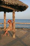 Vrouw in hoed op het strand stock fotografie