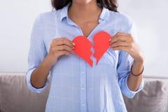 Vrouw Holding Gebroken Rood Valentine Paper Heart Royalty-vrije Stock Afbeelding