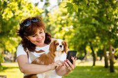 Vrouw, hond en mobiele telefoon stock fotografie