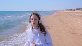 Vrouw in hoofdtelefoonsmuziek die op zee zandstrand sport in werking gestelde openlucht opleiding aanstoten stock video