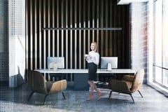 Vrouw in houten en concreet managerbureau stock afbeeldingen
