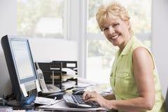 Vrouw in huisbureau bij computer het glimlachen Stock Afbeeldingen