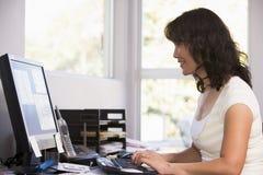 Vrouw in huisbureau dat computer en het glimlachen gebruikt Royalty-vrije Stock Foto