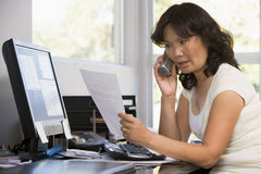 Vrouw in huisbureau met administratie op telefoon Stock Afbeelding