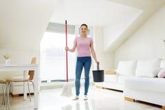 Vrouw of huisvrouw met zwabber schoonmakende vloer thuis Royalty-vrije Stock Afbeelding