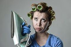 Vrouw of huisvrouwen droevig bored en beklemtoond het houden boos en gefrustreerd ijzer Stock Fotografie