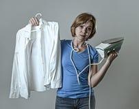 Vrouw of huisvrouwen droevig bored en beklemtoond het houden wit boos en gefrustreerd overhemd en ijzer Stock Foto's