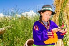 Vrouw, in Indisch kostuum op Uros eiland Peru stock foto's