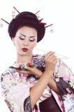Vrouw in Japanse kimono met eetstokjes en sushibroodje Stock Afbeeldingen