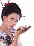 Vrouw in Japanse kimono met eetstokjes en sushibroodje Royalty-vrije Stock Afbeelding