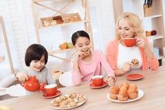 Vrouw in jaren met vrolijke kleinzoon en kleindochter die koekjes eten en thee in rode mokken drinken bij keuken stock afbeelding