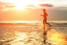 Vrouw jogger bij zonsondergang op de kust Royalty-vrije Stock Afbeeldingen