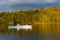 Vrouw Kayaking met Gouden Licht bij Schemer Royalty-vrije Stock Foto's