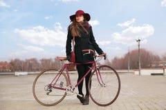 Vrouw in kersenhoed met uitstekende fiets dichtbij moderne concrete architectuur Stock Foto
