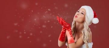 Vrouw in Kerstmankostuum die op sneeuw op een rode achtergrond blazen stock afbeelding