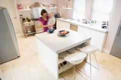 Vrouw in keuken die op tegenholdingsbaby zwaait royalty-vrije stock afbeelding