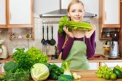 Vrouw in keuken met groene groenten stock afbeelding