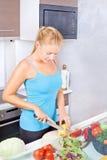 Vrouw in keuken scherpe groenten Royalty-vrije Stock Fotografie