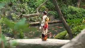 Vrouw in kimono voor koivijver in Tokyo, Japan wordt gevestigd dat stock footage