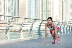 Vrouw klaar te lopen De atleet stelt en maakt de training in werking atletisch Royalty-vrije Stock Foto's