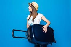 Vrouw klaar voor de zomerreis op blauwe achtergrond wordt geïsoleerd die Mooie vrouw die met bagage op blauwe achtergrond lopen stock foto