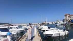 Vrouw in kleding in een Mediterrane haven met velen plezierboot, Frankrijk stock video