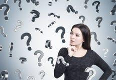 Vrouw in kleding en vraagtekens op grijze muur Stock Afbeeldingen
