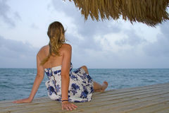 Vrouw in kledingszitting op oceaandok Stock Foto's