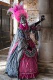Vrouw in kleurrijk roze kostuum en bevederd masker in Venetië Carnaval stock afbeelding