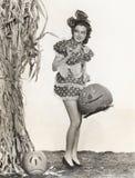 Vrouw in korte stipkleding voor cornstalk dragende pompoen royalty-vrije stock fotografie