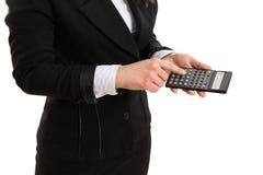 Vrouw in kostuum die een calculator houden en een knoop drukken Stock Fotografie