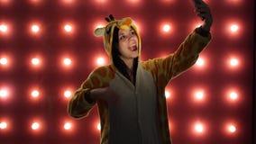 Vrouw in kostuum van giraf op rode achtergrond met gloeilampen Wijfje die een selfie nemen stock video
